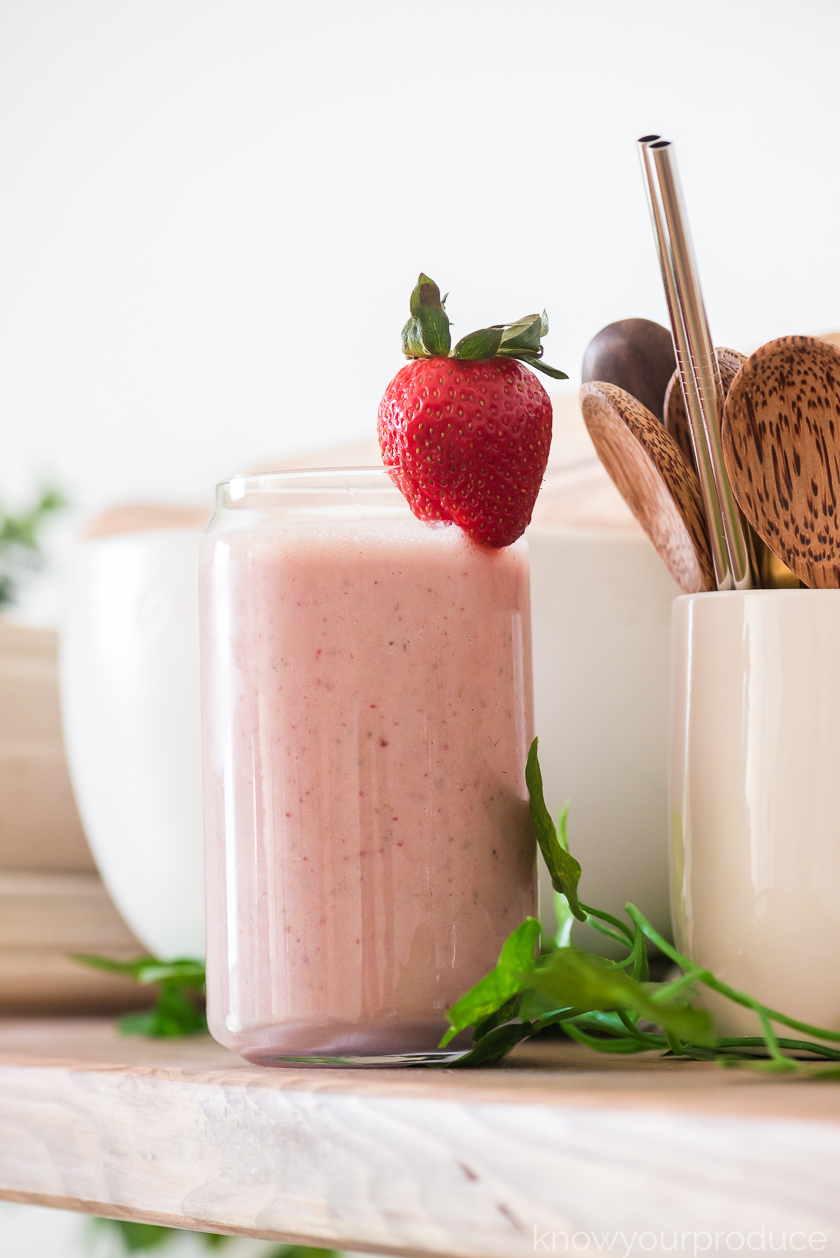 strawberry peanut butter banana smoothie in a glass with strawberry on top on a wooden shelf with small bowls and cup with wooden spoons in background