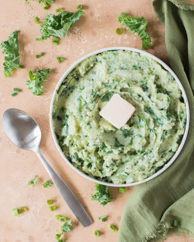 colcannon with tab of butter in a white low bowl with green napkin to the right and spoon to the left on tan backdrop with scattered kale and sliced green onions