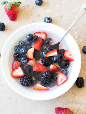 blueberries, strawberries chopped, blackberries, and coconut water in a white bowl with a spoon and berries scattered on a tan backdrop
