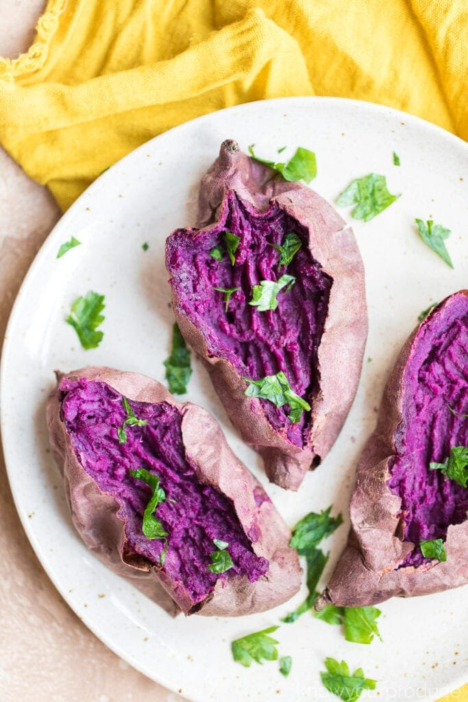 open and fork mashed baked purple sweet potato on a beige speckled plate with fresh parsley on a yellow napkin