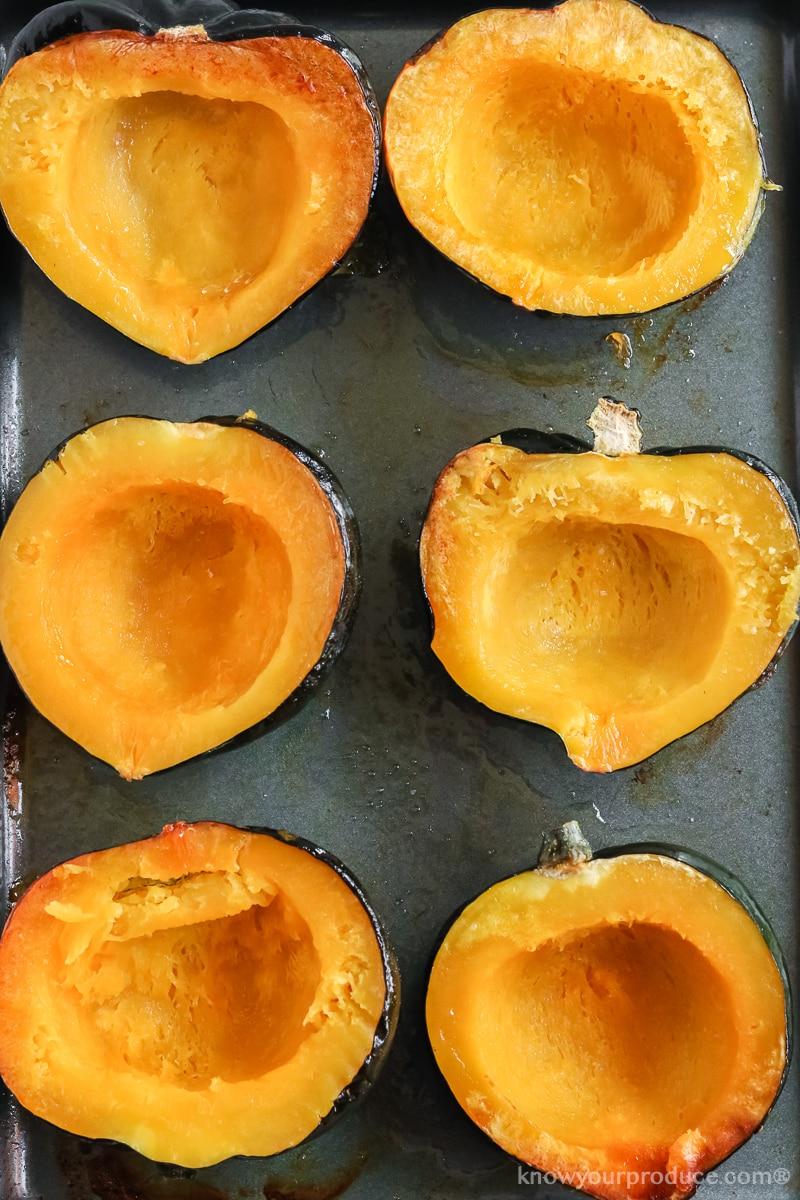 roasted acorn squash halves on a baking sheet pan