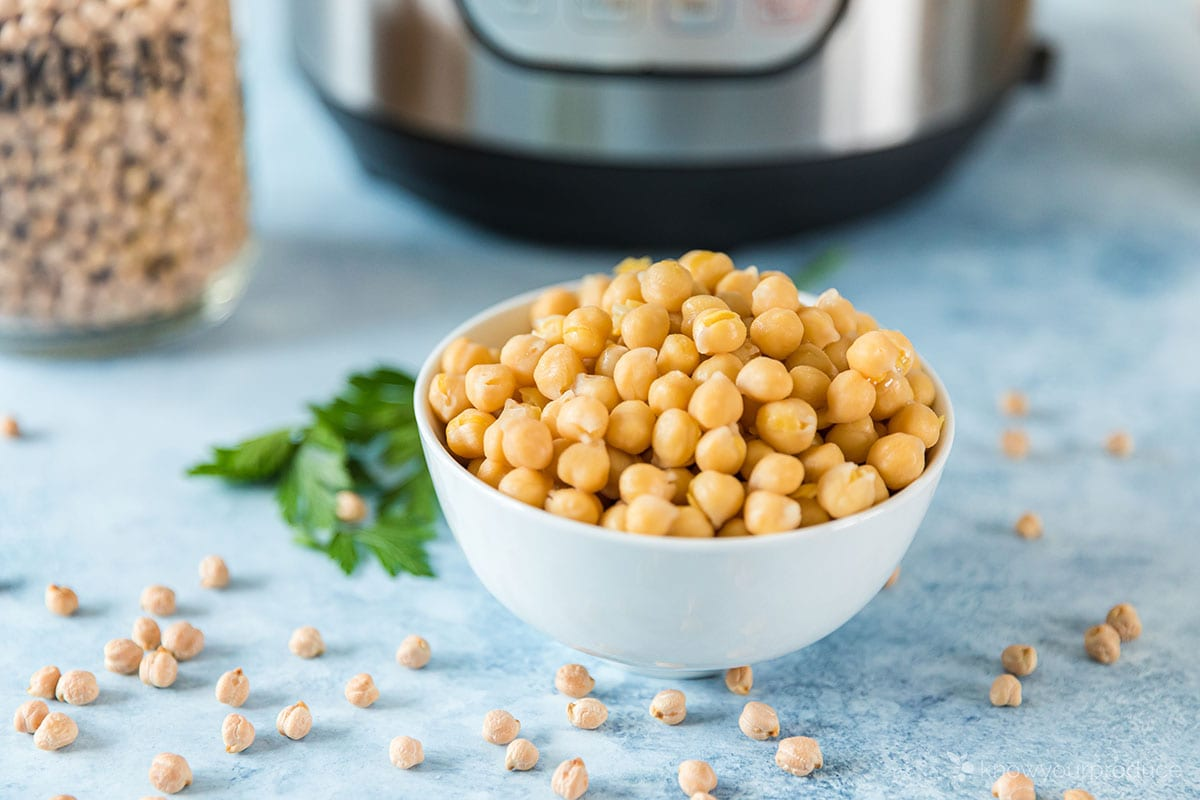 instant pot chickpeas in a white bowl with instant pot in the background