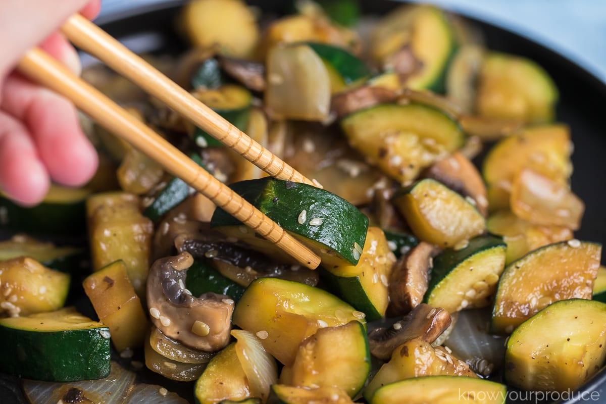 chopsticks grabbing zucchini on plate of hibachi veggies