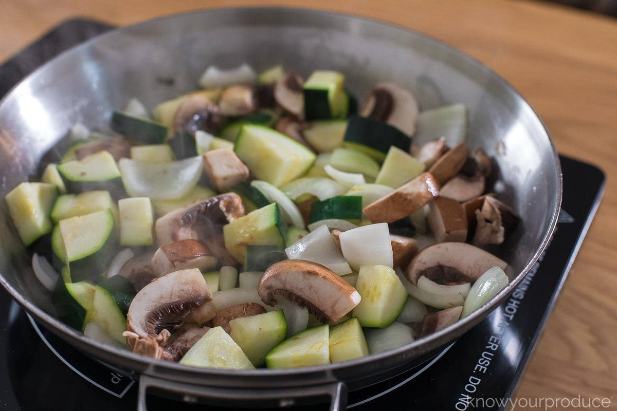 mushrooms, zucchini, and onions cooking in stainless steel skillet