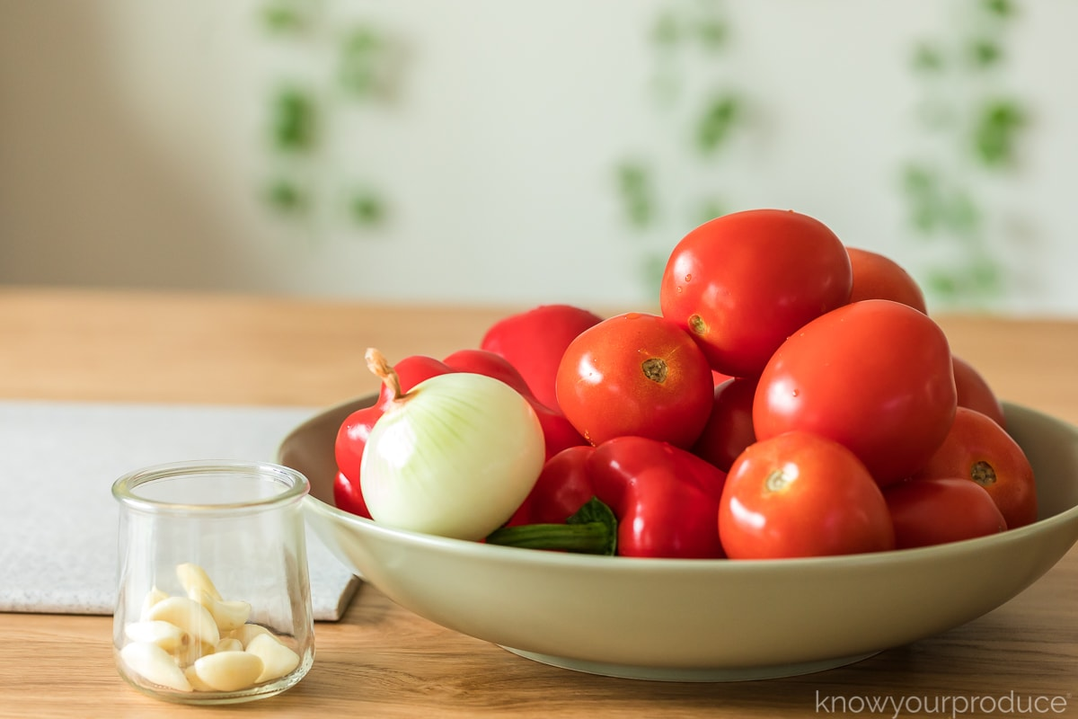 whole roma tomatoes red peppers and onion in a green bowl with garlic cloves in a glass jar to the left