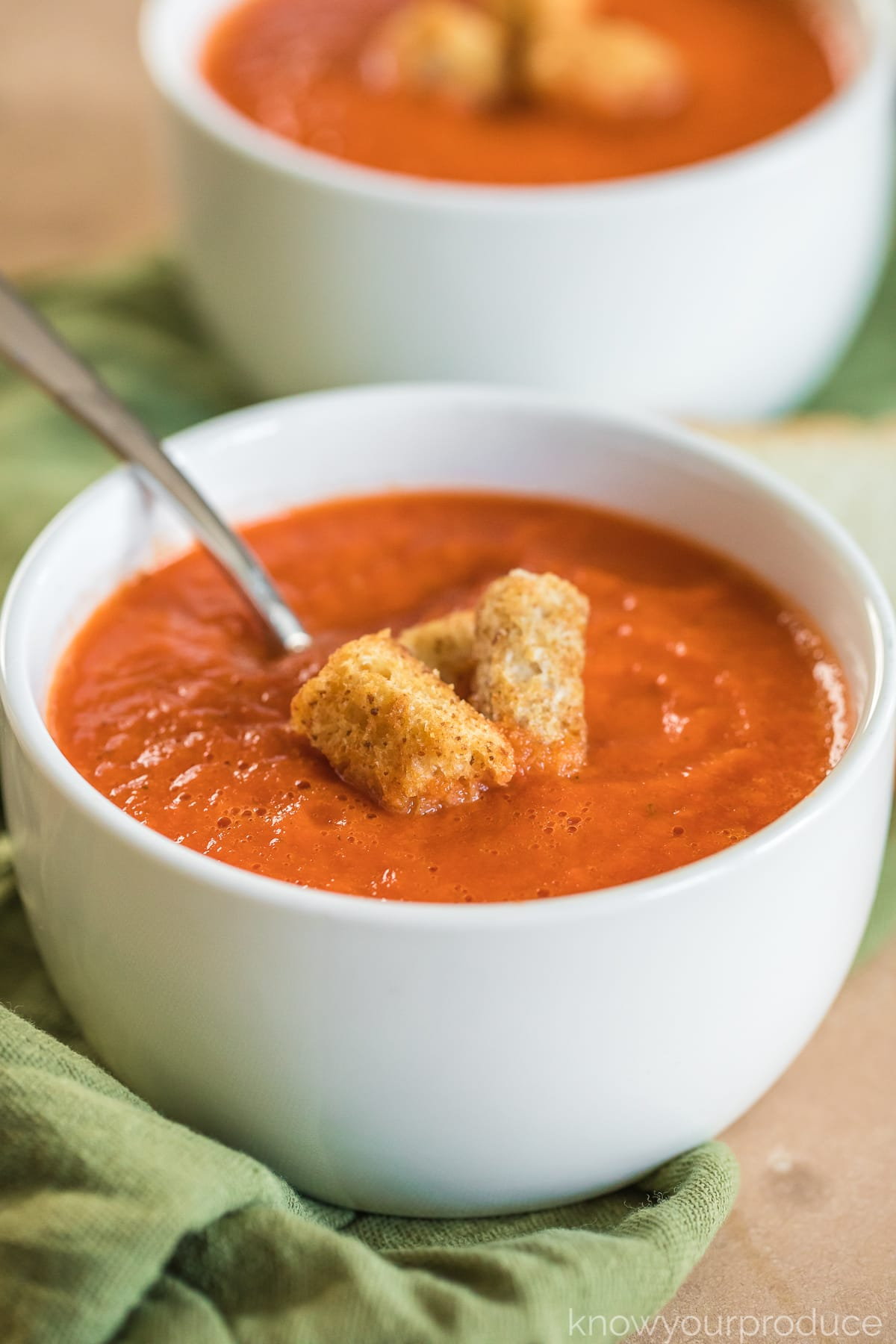 Roasted Red Pepper and Tomato Soup in a white small bowl with croutons and spoon on a green napkin