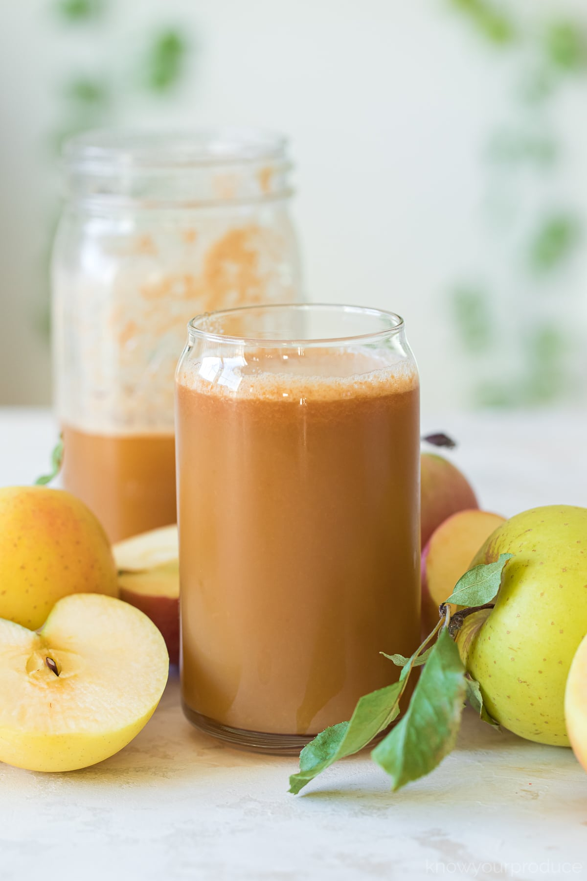 homemade apple cider in a glass cup with apples around it and half filled mason jar behind it