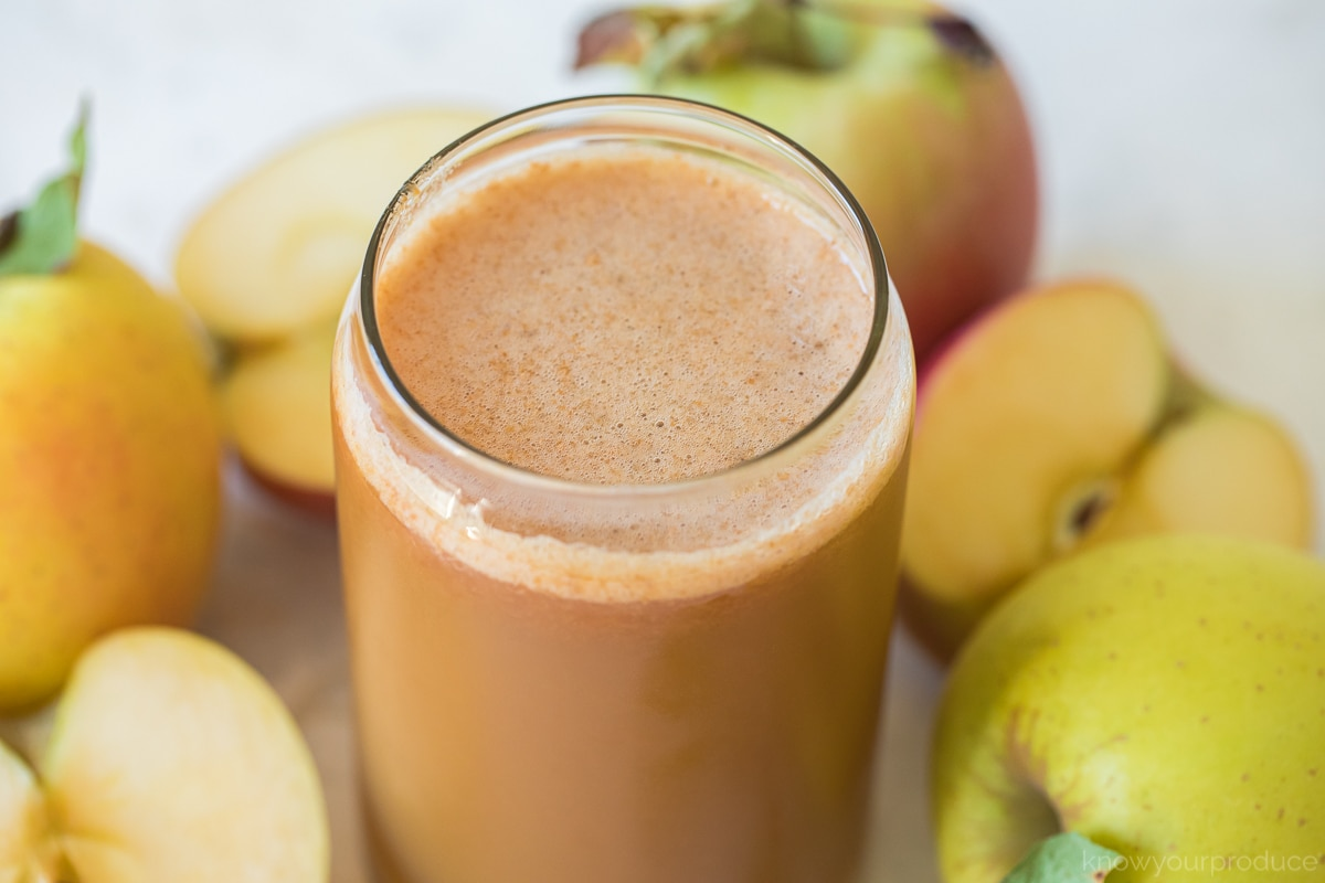 homemade apple cider in a glass cup with apples around it