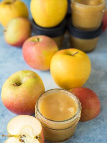 applesauce in small mason jars with apples around it